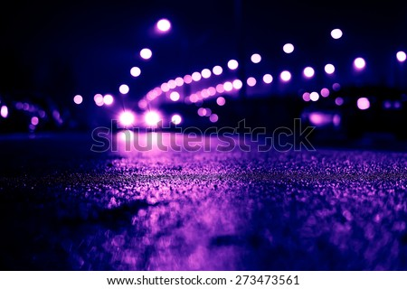 City night lights, road bridge with the lights and moving cars in the fog after rain. View from the level of asphalt, image in the purple-blue toning - stock photo