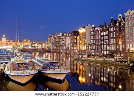 City of Amsterdam in Netherlands at night, historic apartment houses with reflections on water and boats ready for canal tours and cruises. - stock photo