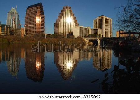 City of Austin Texas downtown at sundown with the sun reflection off the buildings and the buildings reflecting on Town Lake - stock photo