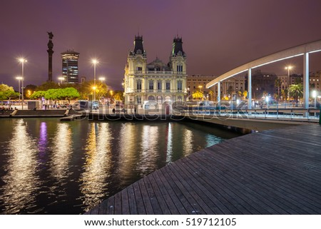 City of Barcelona by night in Catalonia, Spain, view from Rambla de Mar at Port Vell, in skyline Columbus Monument and Old Customs building
