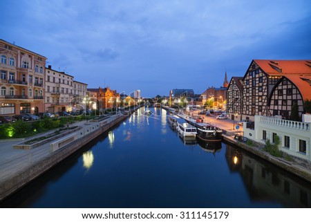 City of Bydgoszcz in Poland by night with old Granaries at Brda river waterfront.