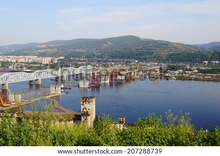 City of Krasnoyarsk view. The Fourth Road Bridge building site on the river Yenisei. Industrial cityscape. Siberia, Russia. Summer day, July 22, 2014.   - stock photo