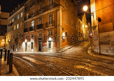 City of Lisbon in Portugal at night, Largo Santa Luzia street with tramline of the famous tram 28. - stock photo