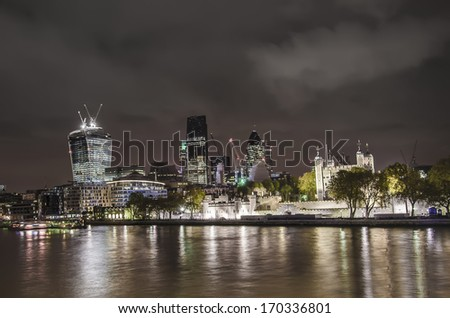 City of London and Tower fortress skyline. The skyscrapers on dramatic sky. Long exposure. Shot in 2013 - stock photo