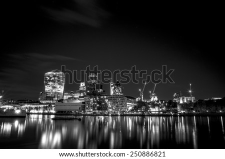 City of London at night reflected in the river Thames. Black and White picture. - stock photo