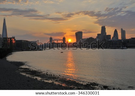 City of London UK at sunset, with river and landmark buildings on skyline - stock photo