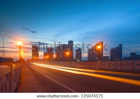 City of Miami Florida, colorful sunset panorama of downtown business and residential buildings and bridge and fast moving traffic - stock photo