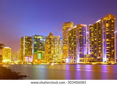 City of Miami Florida, night skyline. Cityscape of residential and business buildings illuminated at sunset with reflection - stock photo
