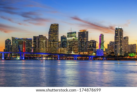 CIty of Miami Florida, summer sunset panorama with colorful illuminated business and residential buildings and bridge on Biscayne Bay  - stock photo