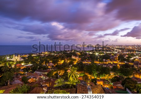 City of Olinda on the foreground with its historic architecture dated from the 14th century and the capital of the state Recife on the far background with its modern architecture at sunset. - stock photo
