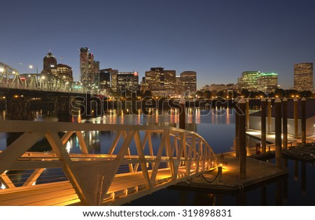 City of Portland Oregon skyline river and pedestrian bridge at twilight. - stock photo