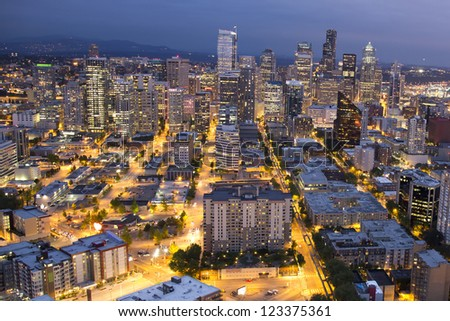 City of Seattle at night, Washington, with neon lights illuminating the big apartment buildings and offices downtown - stock photo