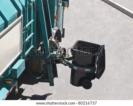 City owned trash truck lifts can with robotic arm. - stock photo