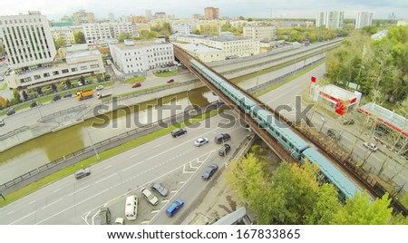 City panorama with overground subway train. View from unmanned quadrocopter. - stock photo