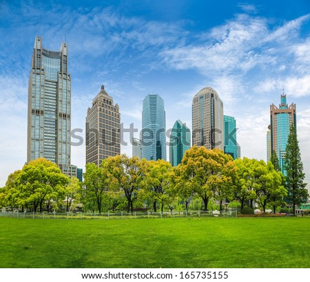 city park greenbelt in shanghai financial center against a blue sky  - stock photo