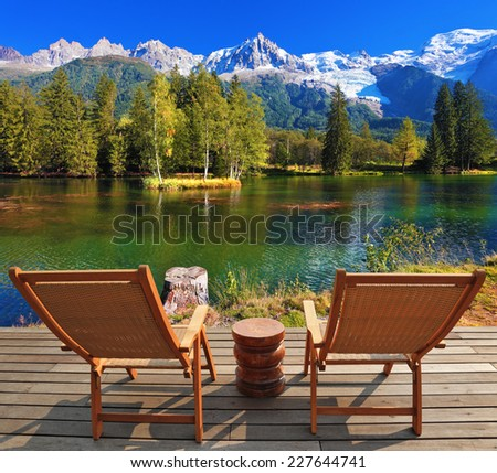City park in the Alpine resort of Chamonix. Comfortable lounge chairs on wooden platform for rest and observation - stock photo