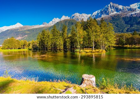 City Park is illuminated by sunset. The lake reflected the snow-capped Alps and evergreen spruce. The mountain resort of Chamonix, Haute-Savoie - stock photo