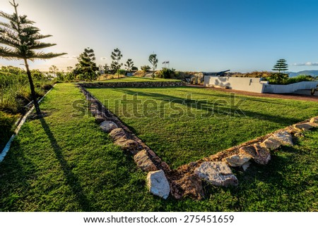 City park on sunset, green lawn, trees, some architectural constructions - stock photo