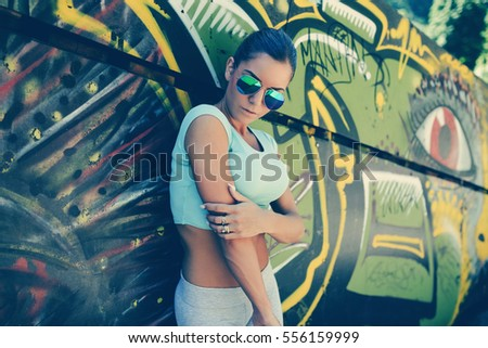 City park outdoors of young attractive woman in jogging timeout. Sport and recreation theme.