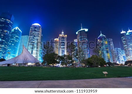 city park with modern building background in shanghai at night - stock photo
