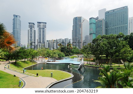 City park with modern buildings in Downtown of Kuala Lumpur - stock photo