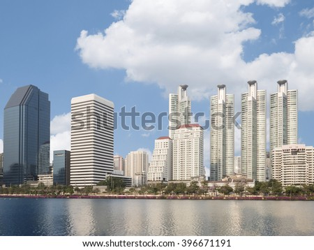 City park with skyscrapers and modern building under blue sky in Bangkok, Thailand (Benjakitti park)