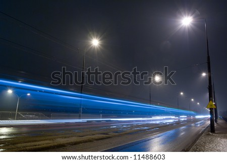 City road by night - rainy weather, blurred car lights. - stock photo