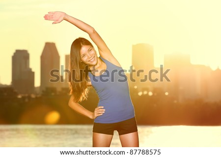 city runner stretching during exercising outdoors in city park with skyline in background. Beautiful young mixed race Asian / Caucasian fitness model training outside. From Montreal, Quebec, Canada. - stock photo
