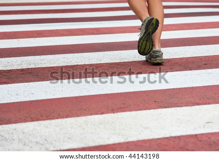 City Running. Closeup of woman running shoes in action on crosswalk in urban setting. Lots of copy space.