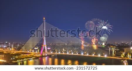 City scape of Rama VIII Bridge at night in Bangkok and Chopraya river and fireworks Festival , Thailand - stock photo