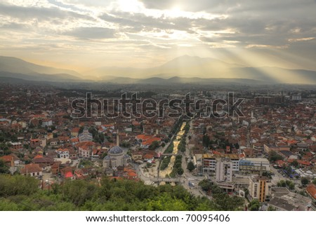 city scape of second biggest city Prizren in Kosovo at sunset with red roofed houses and mosques and river. In the background a mountain range. - stock photo