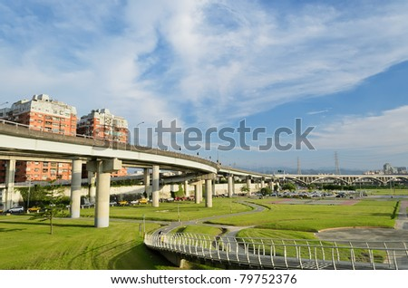 City scenery with highway bridge and apartment buildings with green park under blue sky in daytime in Taipei, Taiwan, Asia.