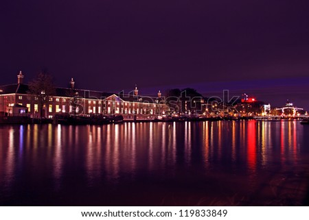 City scenic from Amsterdam at the river Amstel with the Thiny bridge in the Netherlands at night