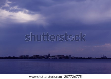 City skyline across a lake under purple storm clouds. Madison, Wisconsin, Midwest USA. - stock photo