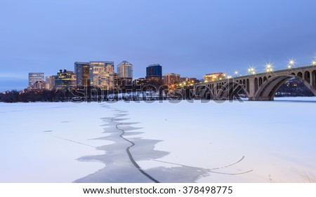 City skyline view of Arlington, Virginia and the Key Bridge across the frozen Potomac River from Georgetown in Washington, DC. - stock photo