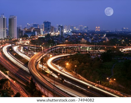 City skyline with multiple flyovers over full moon. Busy traffic light trails. - stock photo