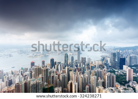 city skyscrapers besides a wide river under black clouds