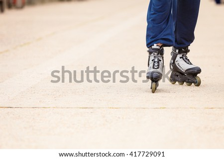 City sports and outdoor activities. Healthy lifestyle exercising and wellbeing. Free time hobby and having fun. Close up on legs in sportswear riding rollerblades. - stock photo