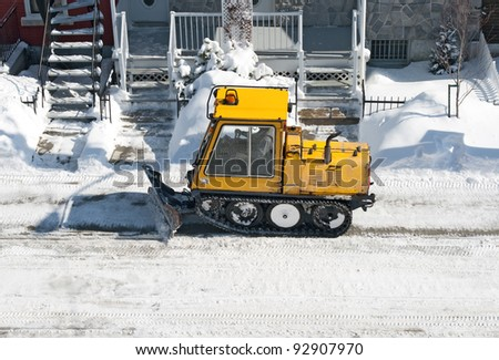 City street cleaned from snow by a snowplough during wintertime. - stock photo