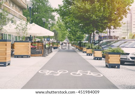 City street with long bicycle lane near outdoor cafe; Sunny effect