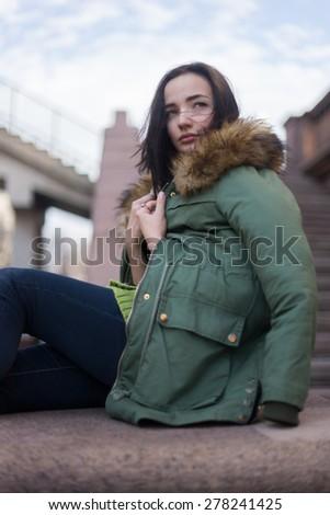 City stylish portrait of beautiful woman posing at the street, nice fall autumn day. Wearing bright green casual jacket. - stock photo