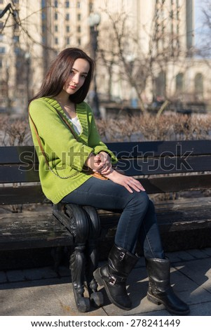 City stylish portrait of beautiful woman posing at the street, nice sunny fall autumn day. Wearing bright green casual sweater. - stock photo