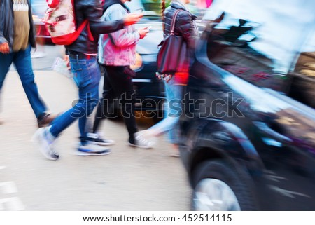 city traffic scene with pedestrians and car in motion blur
