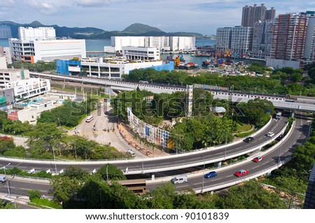 city traffic system - curve turning roads with vehicles and straight railway with a train passing - stock photo