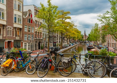 City view of Amsterdam canal and bridge with bikes, typical houses, church and boats, Holland, Netherlands. - stock photo