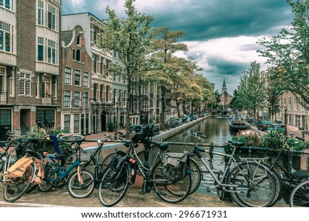 City view of Amsterdam canal and bridge with bikes, typical houses, church and boats, Holland, Netherlands.. Toning in cool tones - stock photo