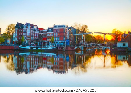 City view of Amsterdam, the Netherlands at sunrise with Amstel river - stock photo