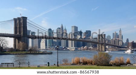 city view of New York (USA) behind the East River and Brooklyn Bridge in sunny ambiance