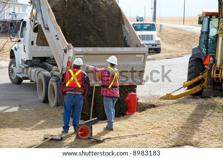 City workers filling in a hole with gravel, around a new hydrant. - stock photo