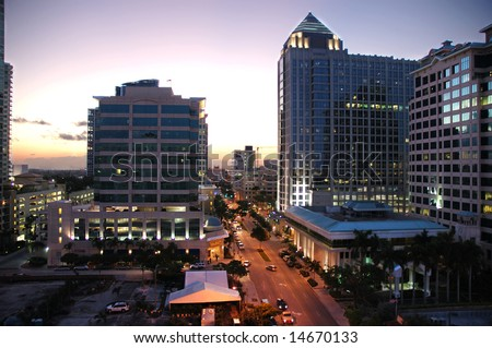 Cityscape at dusk with office buildings and light traffic in downtown Fort Lauderdale, Florida.
